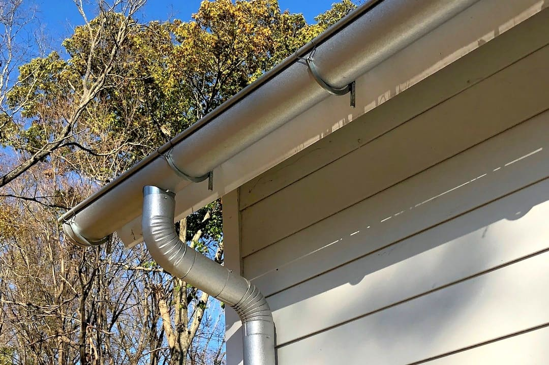 half-round gutter and downspout hung on the side of a house